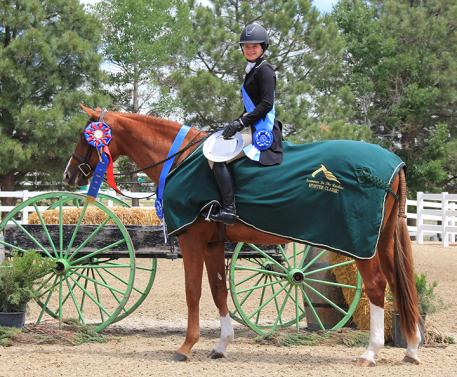 Sixteen-year-old Madeline Porter, riding Cellestine of Dragonfly Farms accepts The Triple Crown Excellence Award