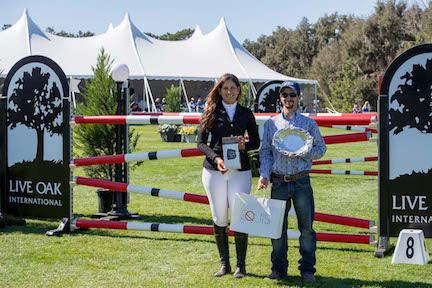 "Anna Christina Gansauer of Ecuador is presented with the Equis Boutique ""Best Presented Horse"" Award for her mount Delgado van't Neerhof. She received prizes from Equis Boutique partner brands from Joe Wasmer of Equis Boutique during the Live Oak International."