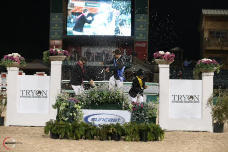 The top three riders spray each other with celebratory champagne following the presentation ceremony.