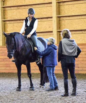Maryal Barnett and Bettina Drummond explain to Julie Arkison, a professional riding instructor from Michigan, their different approaches in helping riders understand use of the seat.