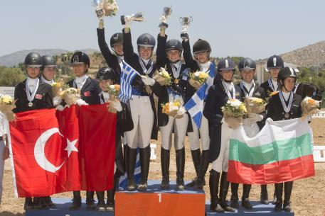 A happy moment on the podium during the presentation of the Junior Team medals at the FEI Balkan Dressage Championshps 2016 in Athens (GRE) last weekend. (L to R): Bulgaria's bronze medallists Stephanie Neseva, Irina Nikolva, Mirela Raikova and Katerina Tvetanova; the newly-crowned Greek champions Elisavet Maika, Lavinia Macropoulou, Eleni Retsou and Theodora Livanos: and Turkey's silver medallists Dila Akbackaloglu, Iren Kaplan, Derin Lara Ekici and Lara Tumay. (FEI/Alexis Valilopoulos)