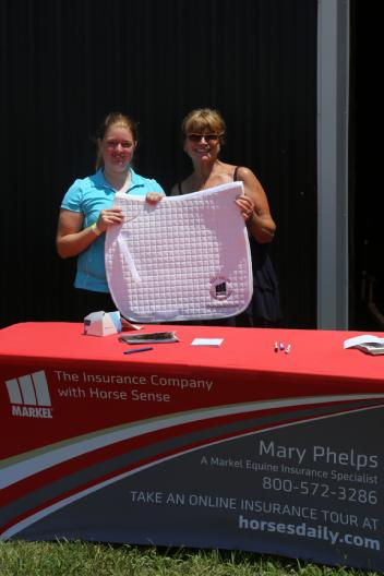 Sponsor Mary Phelps presents Markel Back on Track Saddle Pad to raffle winner Meghan Palensky of Fox Lair Sport Horses.