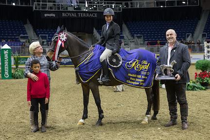 Raphaelle Ferreira of Prevost, QC, accepts the Royal Pony Jumper Championship from Marion Cunningham and William Tilford of Marbill Hill Farm after a second-place finish on Sunday at the Royal Horse Show®.