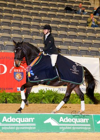 Susan Jones of Kentucky and her Oldenburg gelding Reliance celebrate their win in the Fourth Level Freestyle Adult Amateur Championship.