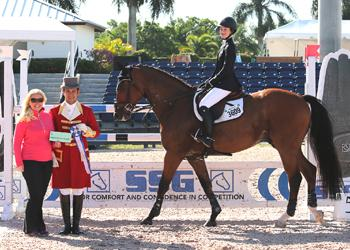 "Daisy Farish, 14, won her second consecutive 0,000 High Junior Jumper Classic.  For wearing SSG 'Digital' riding gloves on her way to victory, Farish was presented with her second consecutive ,000 bonus from Jennifer Ward, accompanied by Gustavo Murcia, in the SSG Gloves ""Go Clean for the Green"" promotion. Photo by Sportfot"