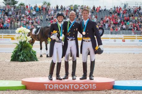 Laura Graves (left), and Steffen Peters (middle) of the United States, with Chris Von Martels (right) of Canada, celebrate their individual Freestyle victories in the 2015 Pan Am Games at Caledon Pan Am Equestrian Park (Photo: FEI/StockImageServices.com)