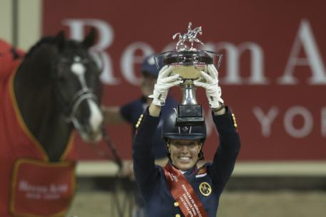 Great Britain's Charlotte Dujardin holds the new Reem Acra trophy aloft after making it a back-to-back double of victories with the amazing Valegro at the Reem Acra FEI World Cup™ Dressage 2015 Final (FEI/Dirk Caremans)