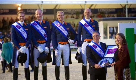 The Dutch team celebrate victory in the third leg of the FEI Nations Cup™ Dressage 2015 pilot series in Rotterdam, The Netherlands (L to R): Edward Gal, Diederik van Silfhout, Patrick van der Meer and Hans Peter Minderhoud. Dutch Chef d'Equipe, Wim Ernes, accepts the trophy from Show President, Belle de Bruin. (FEI/Arnd Bronkhorst)