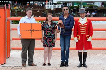 Emanuel Andrade, 18, of Venezuela is presented with the Hermes Talented Young Rider Award.  From left to right:  James Sardelli, Senior Equestrian Account Manager of Hermes; Monique Connelly, Equestrian Specialist for Madison Ave. Hermes Boutique; Emanuel Andrade; and ringmaster Gustavo Murcia. Photo by Starting Gate Communications