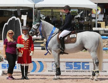 Jennifer Ward, accompanied by ringmaster Gustavo Murcia, presents 17-year-old Kelli Cruciotti with a ,000 bonus from SSG Gloves following her win in the 0,000 Sleepy P Ranch High Junior Jumper Classic on Saturday, March 14. Photo by Sportfot