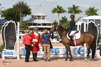 Kelsey Thatcher, mounted on Everything, is presented with a ,000 bonus from Jennifer Ward on behalf of SSG Gloves for wearing SSG 'Digital' riding gloves on her way to victory in the 5,000 SJHOF High Amateur-Owner Jumper Classic at the 2015 Winter Equestrian Festival in Wellington, FL.  Photo by Sportfot