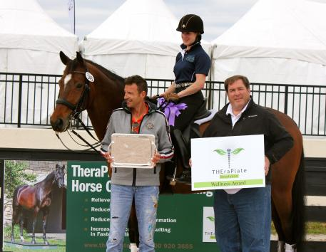 Crystal Kroetch and her coach Albrecht Heidemann smile at the Hanoverian Lymrix, who is presented with the TheraPlate Award by Chip Kreiling of TheraPlate Revolution