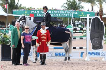 "Ed James, owner of SSG Gloves, and promotion manager Jennifer Ward, accompanied by ringmaster Gustavo Murcia, present Nick Dello Joio, mounted on Contiki, with a $3,000 bonus won in the SSG Gloves ""Go Clean for the Green"" promotion following his win in the $34,000 Ruby et Violette WEF Challenge Cup Round X. (Photo:Sportfot)"