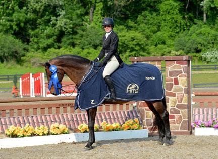 Patricia Griffith and Bellagio, owned by Zoe Ganek, are presented with the blue ribbon after winning the $5,000 Devoucoux Hunter Prix at HITS-on-the-Hudson II, Saturday, May 30, 2015. (c) ESI Photography