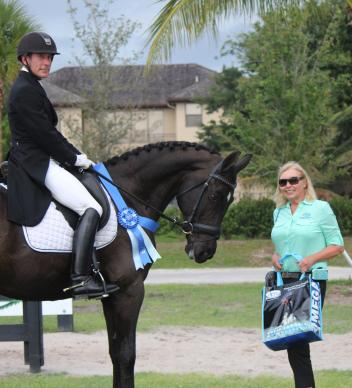 Ryan Yapp and Magic Moments (left) receive the Omega Alpha Healthy Horse Award from Patti Hanco (right) of Omega Alpha Pharmaceuticals Inc