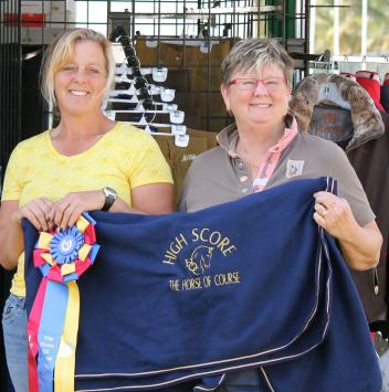 Beth Haist (right), CEO of The Horse of Course, presents the Horse of Course High Score Award to Sara Schmitt (left) at the 2015 AGDF