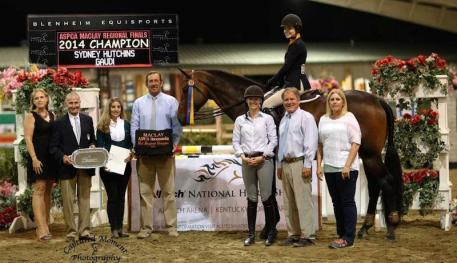 Sydney Hutchins and Gaudi, pictured with (l-r) Melissa Brandes of Blenheim EquiSports, George Morris, Ecole Lathrop, Archie Cox, and Elvenstar trainers Katie Gardner, Jim Hagman and Kay Altheuser.  Photo courtesy of CapturedMomentPhoto.com