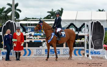 Canada's Vanessa Mannix, riding Valerie F.S., is presented with a ,000 bonus from Jennifer Ward on behalf of SSG Gloves for wearing SSG 'Digitals' on her way to victory in the 5,000 High Amateur-Owner Jumper Classic at the 2015 Winter Equestrian Festival in Wellington, FL.  Photo by Starting Gate Communications