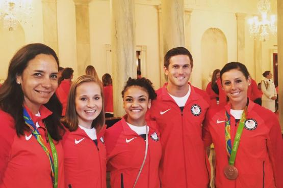 Allison Brock and Kasey Perry-Glass pose with Olympic Gymnasts