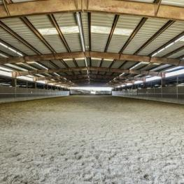 Indoor arena with lights and full short side of mirrors, sand and textile footing