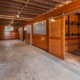 The largest of the three barns was built by Barn Pros and is beautifully remodeled and painted. It has four large 12 ft. x 18 ft. stalls, wash rack, tack room with water and power, and its upper hayloft can hold up to 500 bales of hay. It is outfitted with all new electrical outlets and lighting, including a sensor light on the exterior.