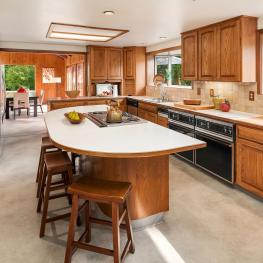 The kitchen also contains a trash compactor, extra sink, wet bar, wall pantry, woodblock counter, two large windows, dropped down florescent lighting, and tile backsplash.