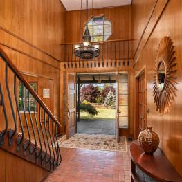 The wood paneling and custom dappled rose-colored glass highlights the entry and filters the warm natural light.