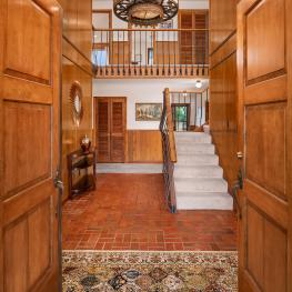 Enter through the custom wood doors into the red brick floored foyer and see the unique wood and wrought iron railing accompanying the staircase.