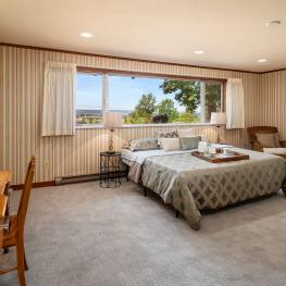 The first upstairs bedroom or bonus room is incredibly spacious, with baseboard heating, new carpet, double closet, huge windows, tile window sills, and great panoramic views.