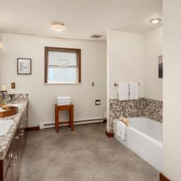 The gigantic hall bath sits directly between the four bedrooms and contains a newly coated shower and tub, tile counters, new toilet, double sinks, and a tile silled window.