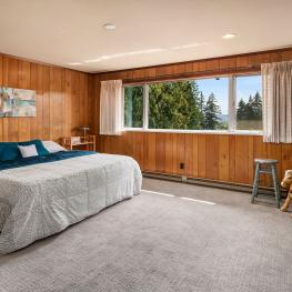 The third upstairs bedroom is quite sizeable and has baseboard heating, walk-in closet, large tile silled window, new carpet, and great territorial and some Cascades views.