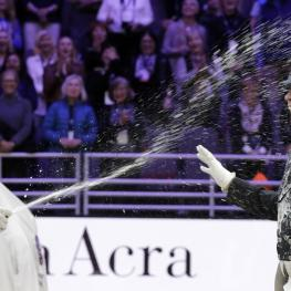 First place winner Isabell Werth (L) from Germany sprays 3rd place winner Carl Hester from Great Britain (R) with Champagne on the podium at the awards ceremony for the Grand Prix Freestyle Dressage Final in the FEI World Cup Finals in Omaha, Nebraska, USA on 01 April 2017.