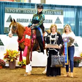 Triple Crown Excellence Award winner Hillary Rapier riding SB Heritage+ in the winner's circle at the Arabian and Half Arabian Sport Horse Nationals