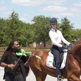 It takes a village: with the help of sponsors Charles Owen, Equiline, and Vita Flex, Grand Prix dressage rider Caroline Roffman dances with her horse as DSharp plays the violin.